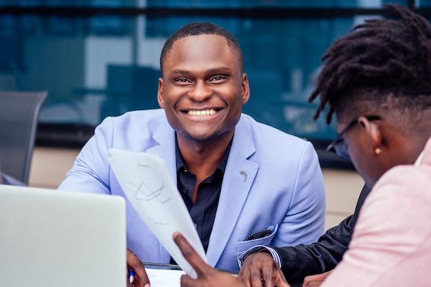 Dwa stylowe african american biznesmen partnerów przedsiębiorców w garniturach mody siedzi przy stole w letniej kawiarni na świeżym powietrzu.