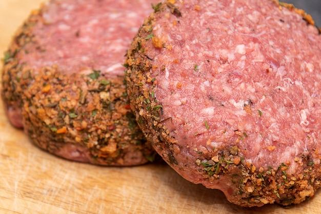Dwa surowe hamburgery jagnięce na drewnianej desce do krojenia. zbliżenie.