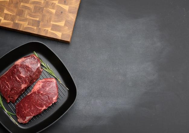 Dwa surowe kawałki wołowiny na czarnej kwadratowej patelni grillowej, steki na czarnej powierzchni, widok z góry, miejsce na kopię
