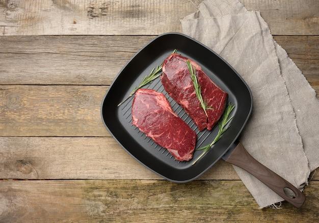 Dwa surowe kawałki wołowiny na czarnej kwadratowej patelni grillowej, steki na drewnianej powierzchni, widok z góry, kopia przestrzeń