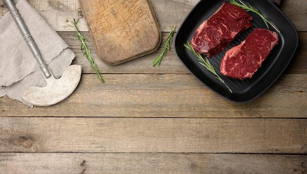 Dwa surowe kawałki wołowiny w czarnej kwadratowej patelni grillowej, deska do krojenia i nóż na drewnianym stole, widok z góry, miejsce na kopię