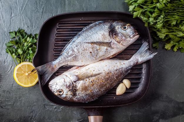 Dwa surowe ryby dorado z przyprawami i cytryną.