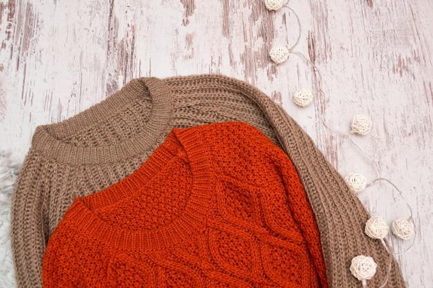Dwa swetry z dzianiny na drewnianym tle. girlanda z rattanowych lampionów. modna koncepcja, zbliżenie