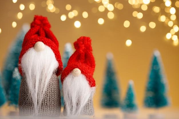 Dwa świąteczne krasnale w czerwonych kapeluszach na złotym tle