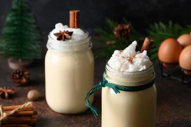 Dwa świąteczne świąteczny napój ajerkoniak w słoiku z przyprawami