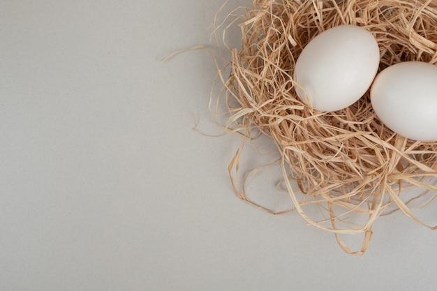 Dwa świeże białe jaja kurze na sianie.
