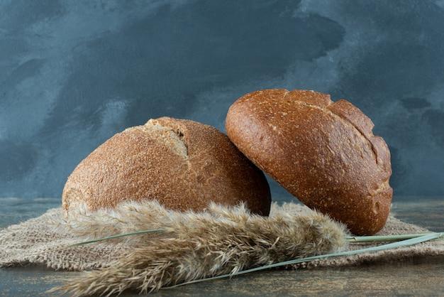 Dwa świeże brązowe drożdżówki z pszenicy na worze