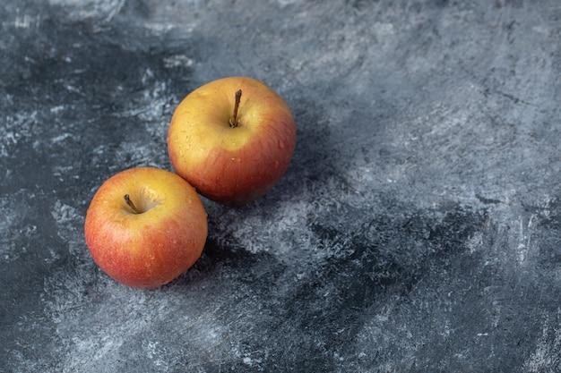 Dwa świeże czerwone jabłka na marmurowym tle.