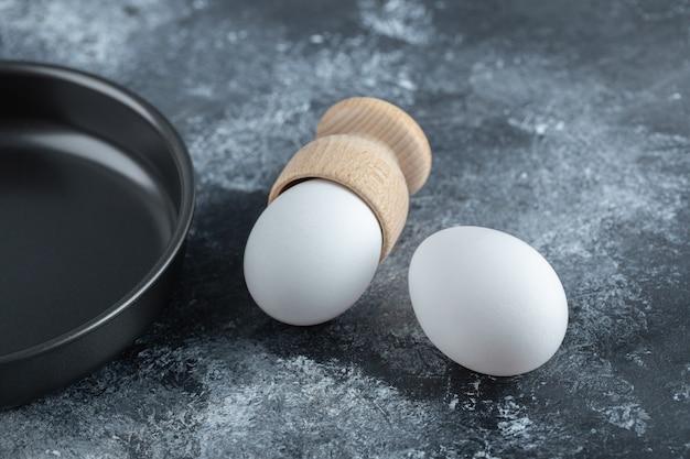 Dwa świeże jajka z patelnią