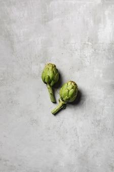 Dwa świeże karczochy na jasnoszarym stole. egzotyczne warzywo dla zdrowego odżywiania i diety.