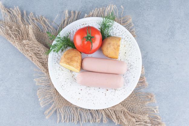 Dwa świeże kiełbasy gotowane na białej płytce z ziemniakami i pomidorami.