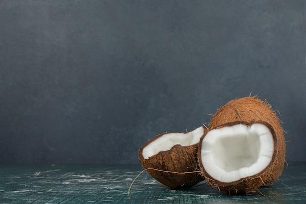 Dwa świeże kokosy na marmurowej powierzchni