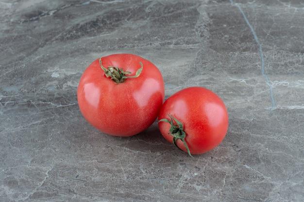 Dwa świeże pomidory na marmurowym stole.