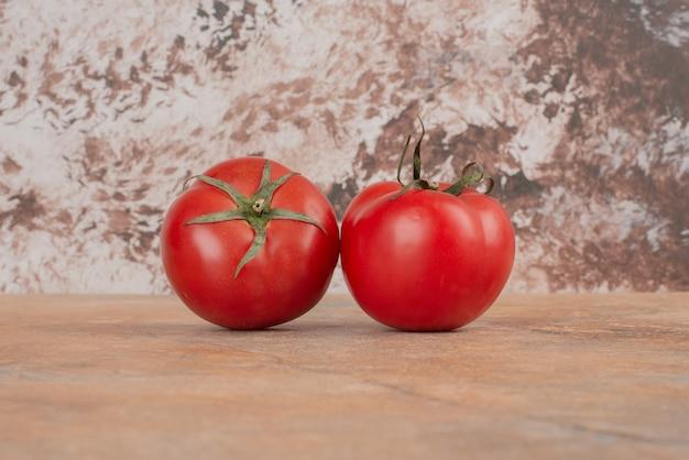 Dwa świeże pomidory wyizolowanych na marmurowym stole.