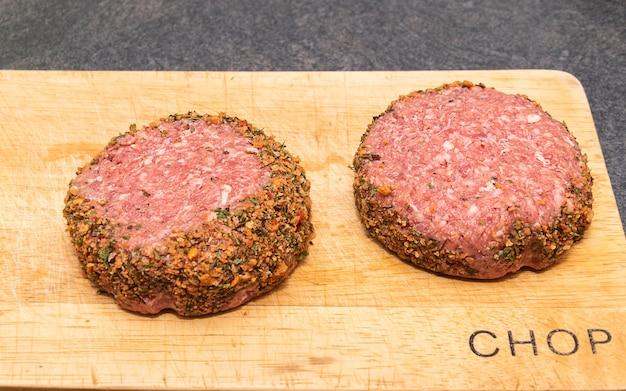 Dwa świeże surowe hamburgery jagnięce na drewnianej desce do krojenia.