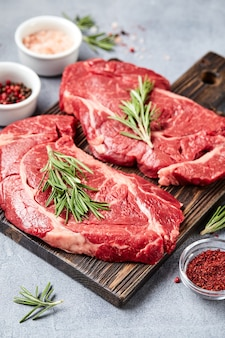 Dwa świeże surowe mięso prime black angus beef steaks, rib eye, denver, na drewnianej desce do krojenia.