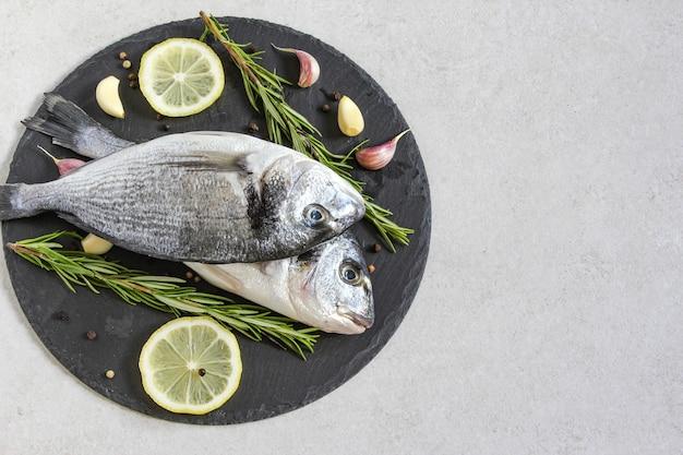 Dwa świeże surowe organiczne dorado morskie lub dorada z przyprawami i cytryną