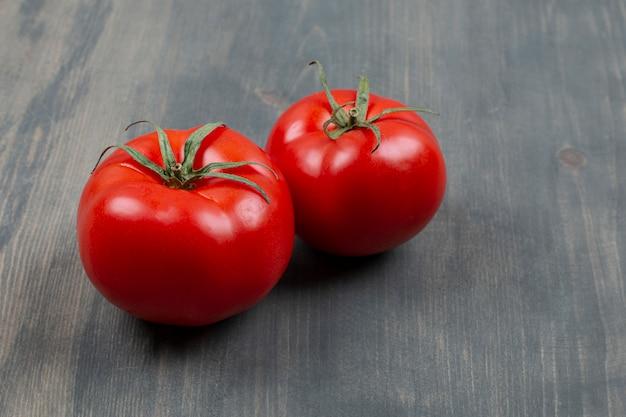 Dwa świeże surowe pomidory z liśćmi na drewnianym stole