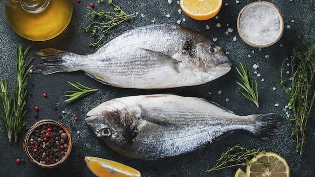 Dwa świeże surowe ryby dorado z przyprawami i oliwą z oliwek na ciemnym stole z kamienia. widok z góry. leżał płasko.