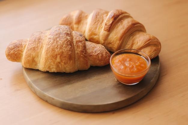 Dwa świeżo upieczone criossant na drewnianym stole w domu. wegański pusty croissant. dżem morelowy na talerzu. domowy rogalik i dżem.