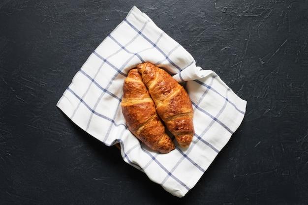 Dwa świeży croissant na kamiennym stole.