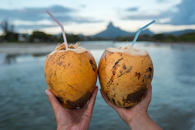 Dwa świeży koktajl kokosowy ze słomką w dłoniach