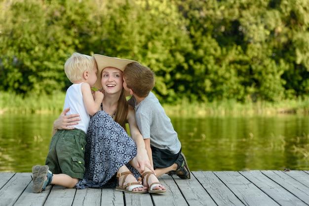 Dwa synek całuje matkę i siedzi na molo na brzegu rzeki