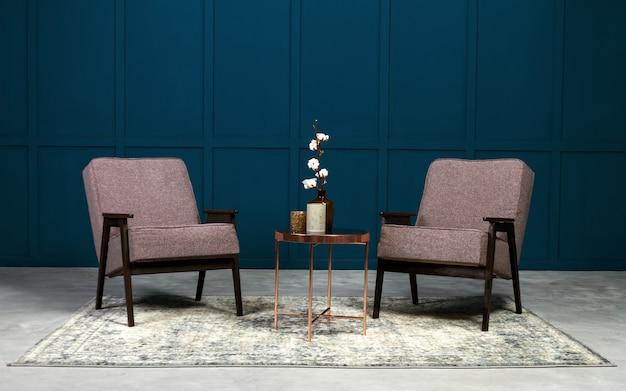 Dwa szary fotel i miedziany stolik kawowy i wazony na nim w niebieskim pokoju