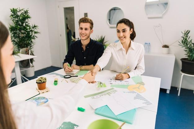 Dwa szczęśliwe bizneswomanu chwiania ręki podczas biznesowego spotkania