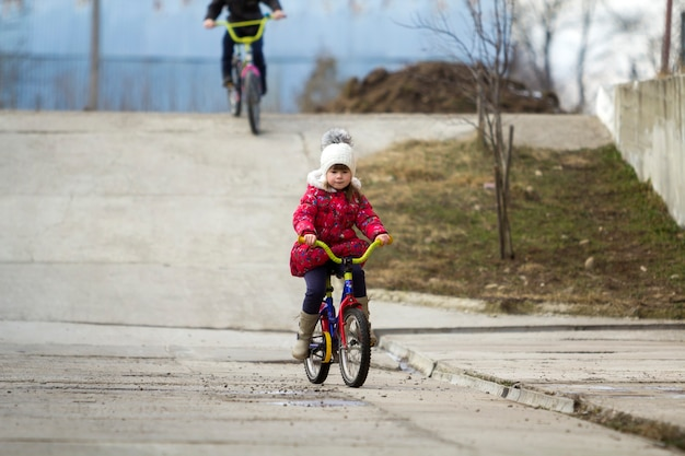 Dwa szczęśliwe dzieci, chłopiec i dziewczynka, jazda na rowerach na zewnątrz w zimnie