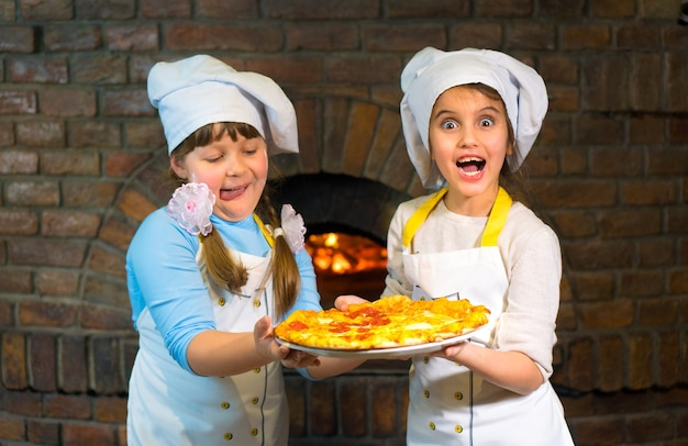 Dwa szczęśliwe dzieciaki w kapeluszach szefa kuchni trzymają razem pizzę na kamiennym piecu