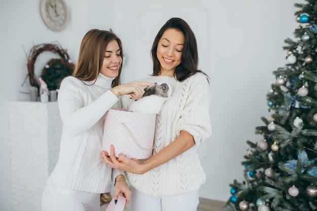 Dwa szczęśliwe dziewczyny otwierają bożenarodzeniowych prezenty.