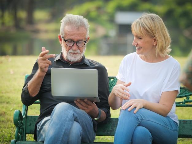 Dwa szczęśliwe emerytów seniorów mężczyzna i kobieta siedzą i przy użyciu komputera laptop w parku