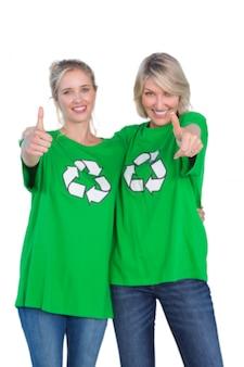 Dwa szczęśliwe kobiety jest ubranym zielonych przetwarza tshirts daje aprobatom