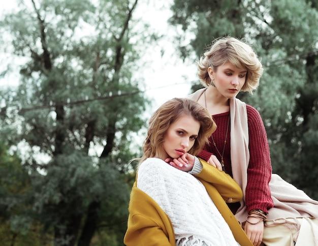 Dwa szczęśliwe ładne młode kobiety, strzelanie do mody. na dworze.