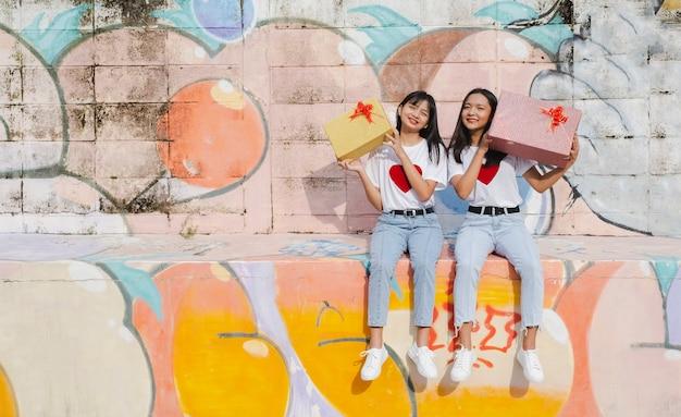 Dwa szczęśliwe młoda dziewczyna z teraźniejszym pudełkiem na kolorowym tle. azjatyckie dziewczyny.