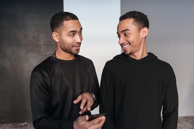 Dwa szczęśliwego afrykańskiego młodego człowieka stoi telefon komórkowego i używa