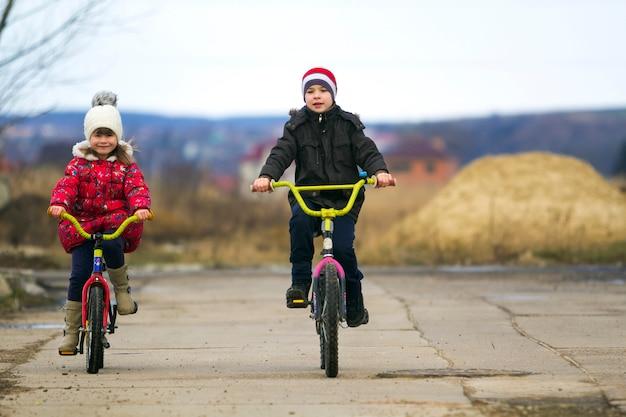 Dwa szczęśliwego dziecka chłopiec i dziewczyna jedzie bicykle outdoors w zimnej pogodzie