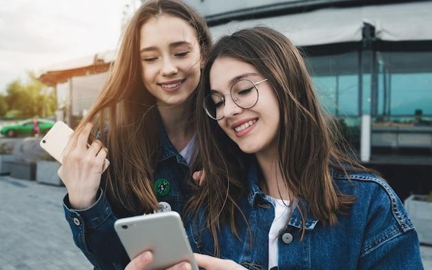 Dwa szczęśliwego młodego najlepszego przyjaciela używa telefony na miasto ulicie