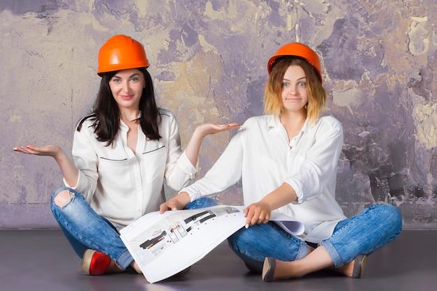 Dwa szczęśliwego śmiesznego ślicznego architekta kobiety kobiety dziewczyna w pomarańczowych budowy ochrony budynku hełmach siedzi na podłoga z architektura rysunkami i szkicami.