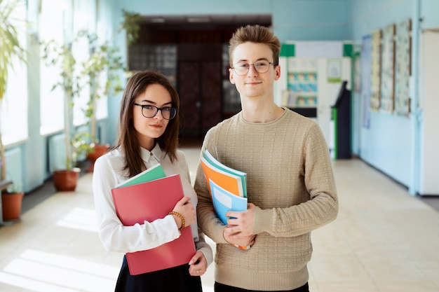 Dwa szczęśliwego ucznia stoi w kampusie patrzeje kamerę