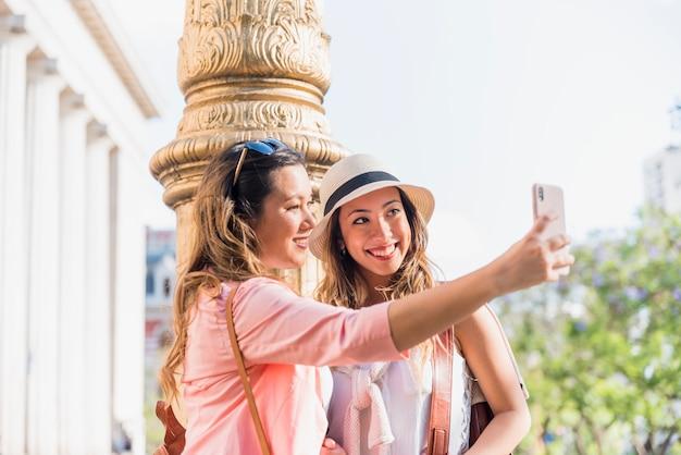 Dwa szczęśliwego żeńskiego przyjaciela bierze jaźń portret od telefonu komórkowego