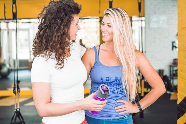 Dwa szczęśliwej dysponowanej kobiety patrzeje each inny w sprawność fizyczna klubie