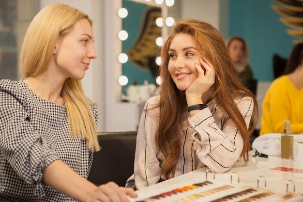 Dwa szczęśliwej kobiety cieszy się dzień przy włosianym salonem