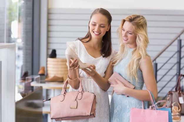 Dwa szczęśliwej kobiety patrzeje pięta but
