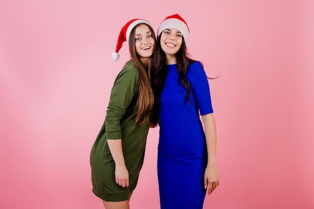 Dwa szczęśliwej kobiety ściska być ubranym santa kapelusze odizolowywających nad menchiami