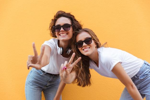 Dwa szczęśliwej rozochoconej nastoletniej dziewczyny w okularach przeciwsłonecznych pokazuje pokoju gestykulują