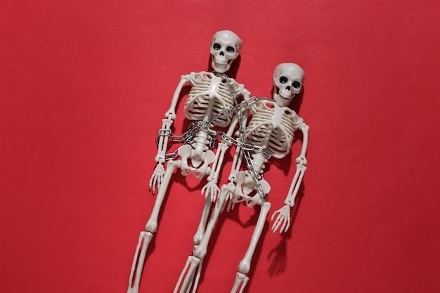 Dwa szkielety owinięte łańcuchem na czerwonym jasnym tle