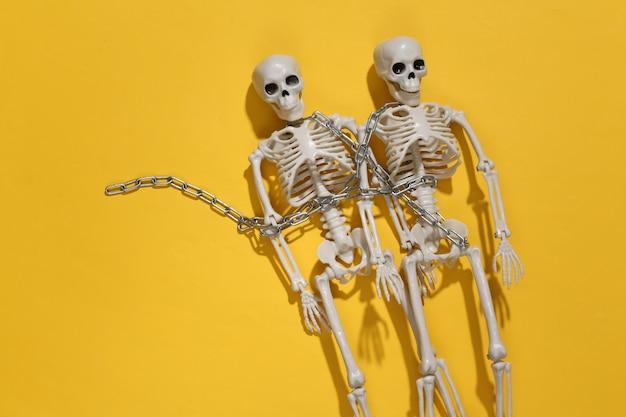 Dwa szkielety owinięte łańcuchem na żółtym jasnym tle