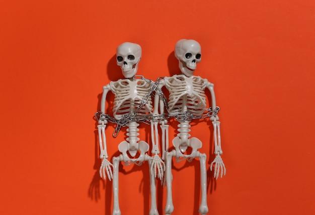 Dwa szkielety owinięte w łańcuch na pomarańczowym jasnym tle.